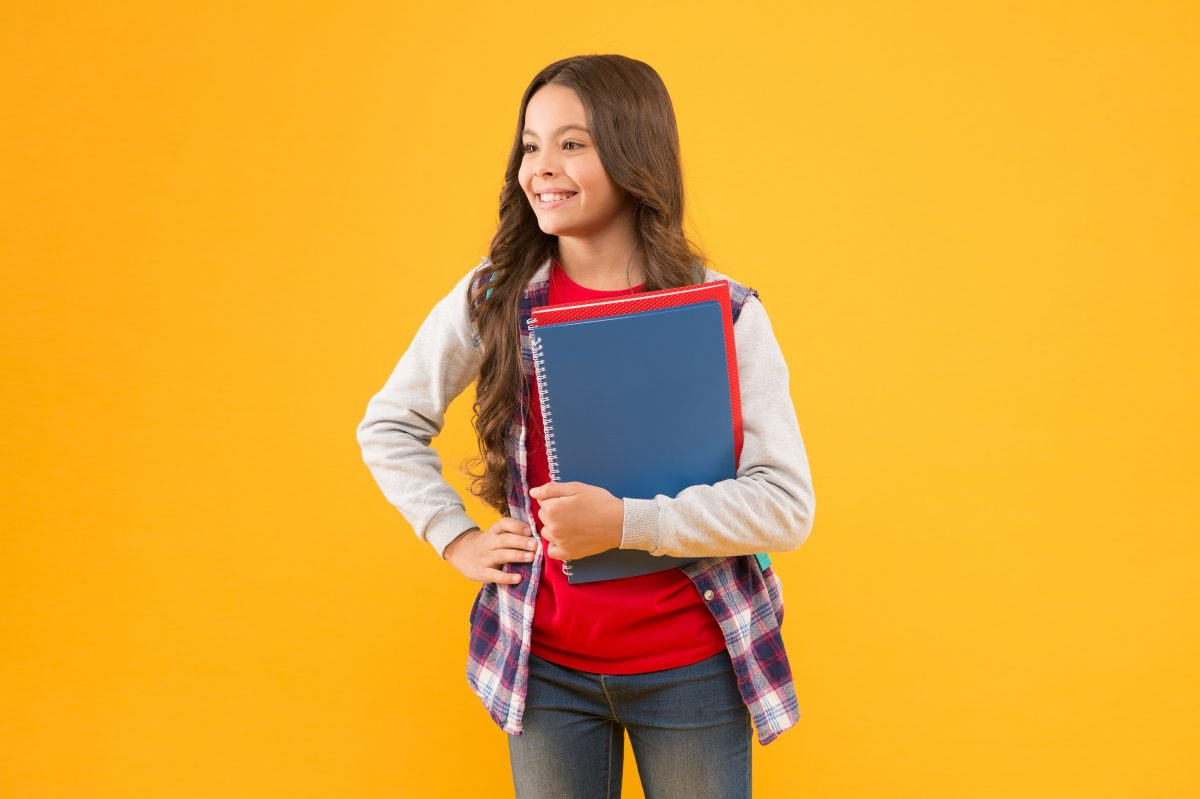 Young teen smiling and holding notebooks