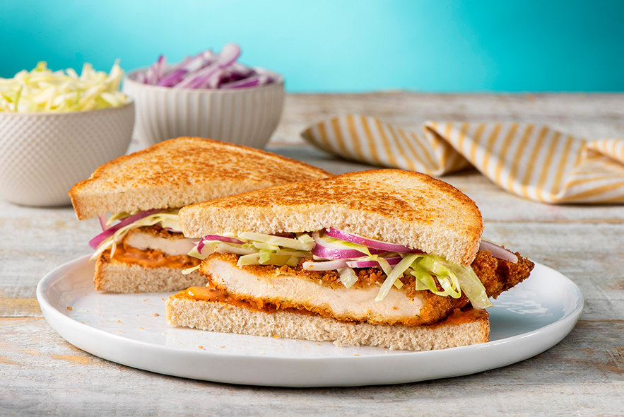 Chicken cutlet sandwich with a bowl of cabbage slaw in the background