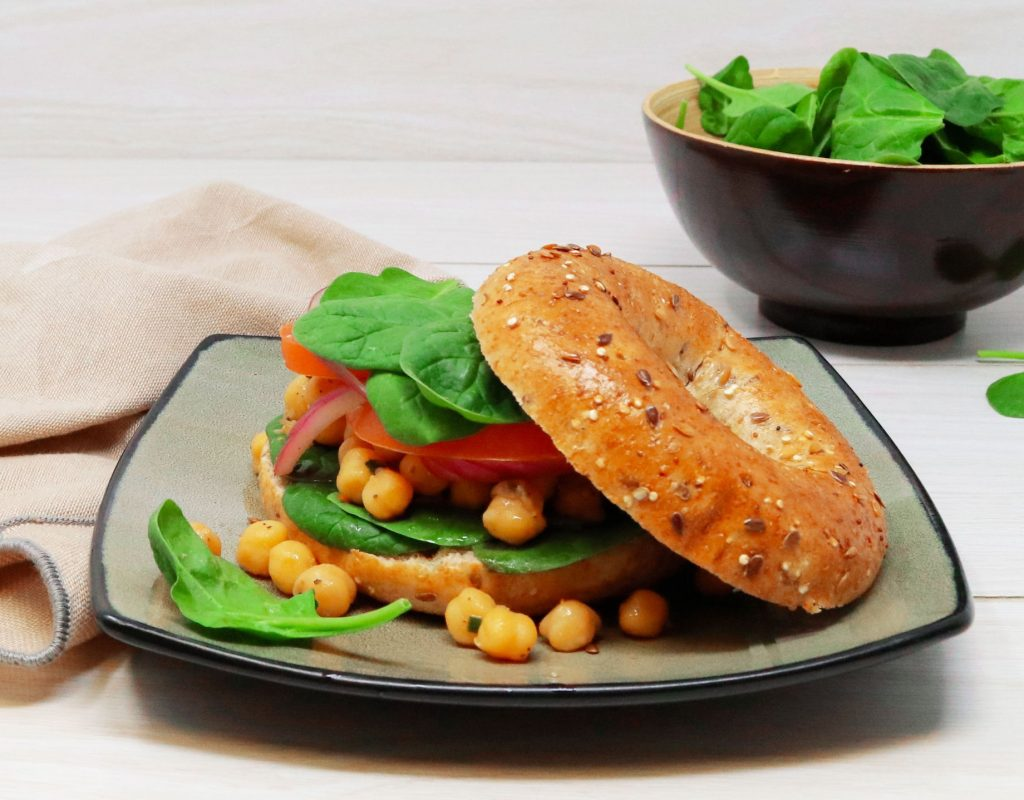 Close up shot of Country Harvest 14 Grain Bagel topped with chickpeas, spinach leaves, red onion and slices of red peppers