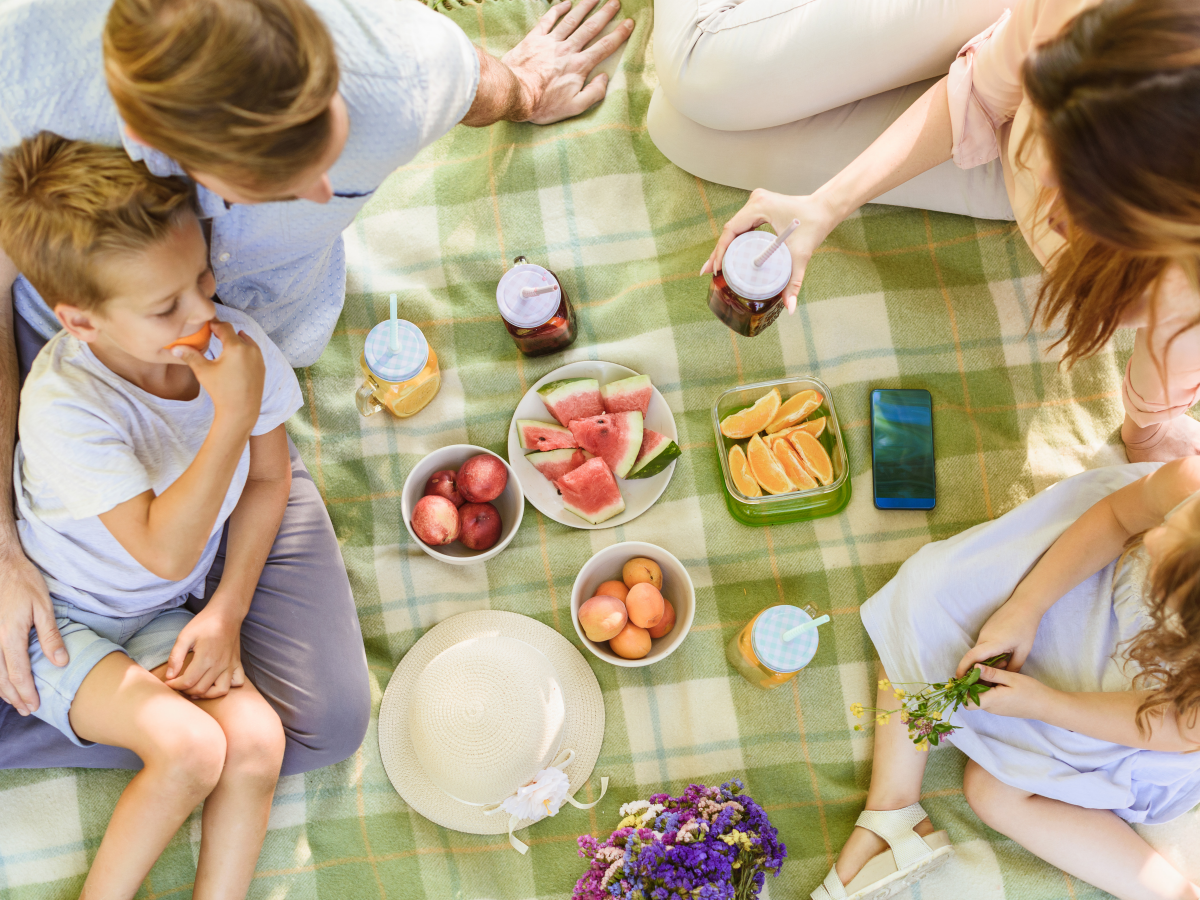 Family of 4 sitting on a green picnic blanket with fruits in the center