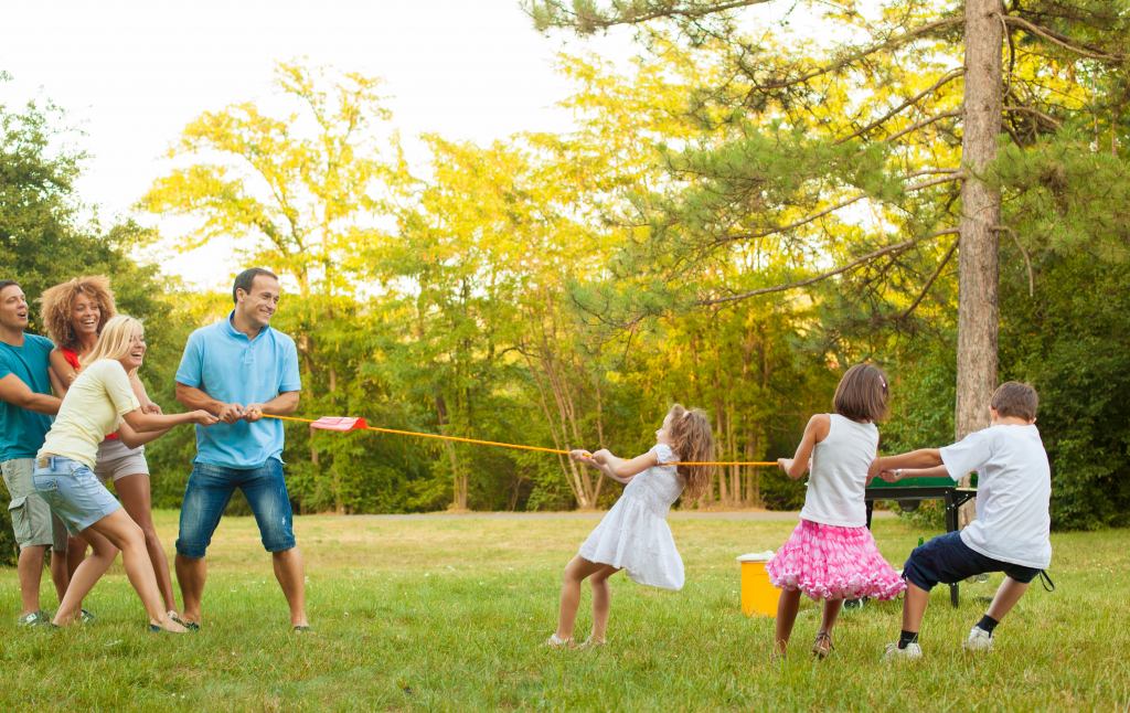 4 adults versus 3 kids playing a game of tug-of-war in a wooded area