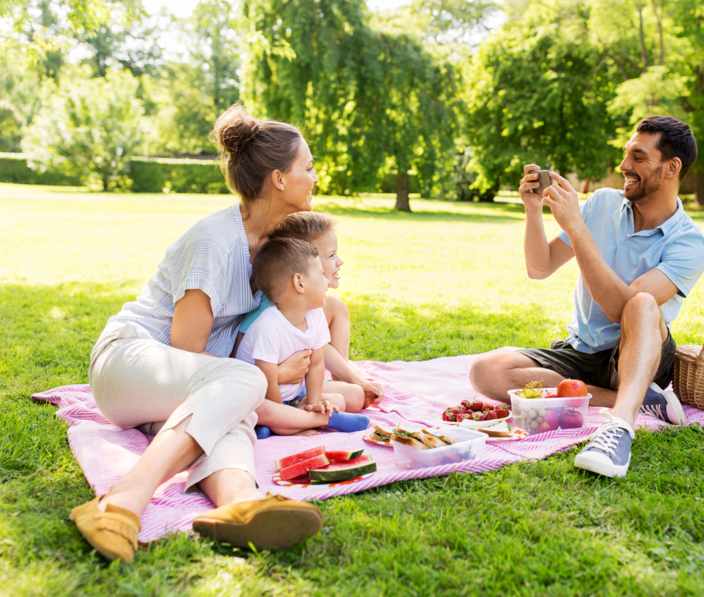 A dad taking a picture of a mom and her 2 kids having a picnic