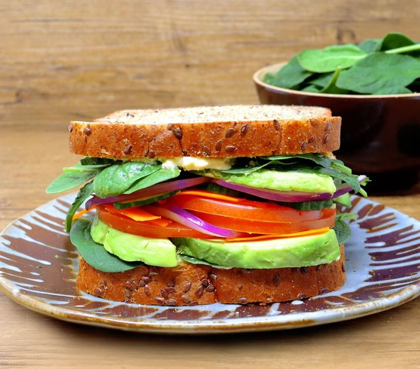 Close up image of a sandwich made with Country Harvest Grains+ Energy topped with avocado, tomatoes, hummus and spinach
