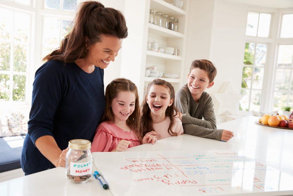 Une mère et trois enfants regardant un tableau blanc avec des tâches